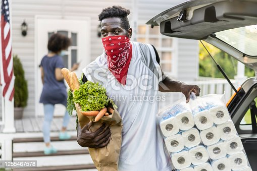 African ethnicity man wearing a bandana to protect his face while unloading grocery bags and toilette paper after arriving from shopping at moment of virus pandemic