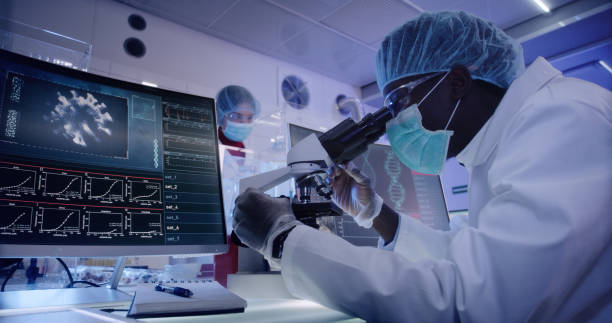 Young african ethnicity microbiologist studying coronavirus. Looking through microscope stock photo