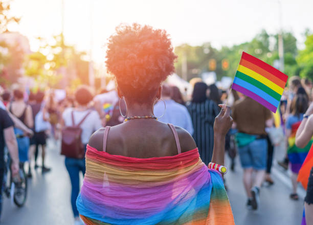 Young African ethnicity woman at the love festival Rear view image of young African-American woman walking at the LGBTQI pride event and waving rainbow flag gay pride parade stock pictures, royalty-free photos & images