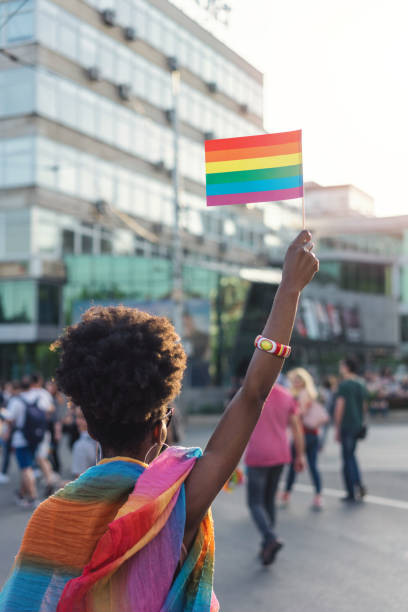 Young African ethnicity woman waving rainbow pride flag at the love festival stock photo