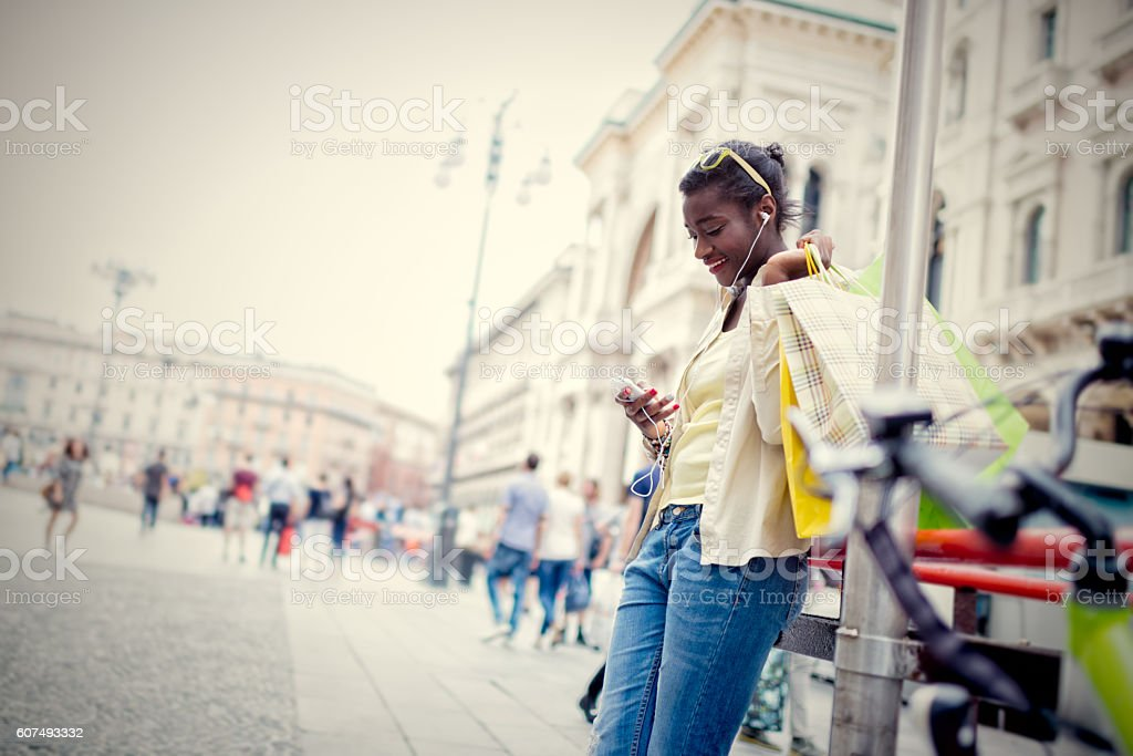 Young African European woman using wifi connection at Duomo Squa stock photo