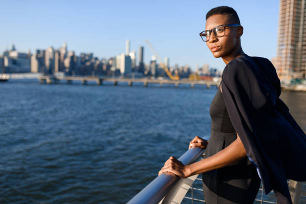 Young african fashionable businesswoman working outdoor, New York, Manhattan view, skyline stock photo