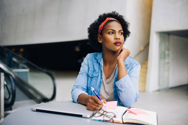 Young African female entrepreneur dreaming up new business ideas stock photo