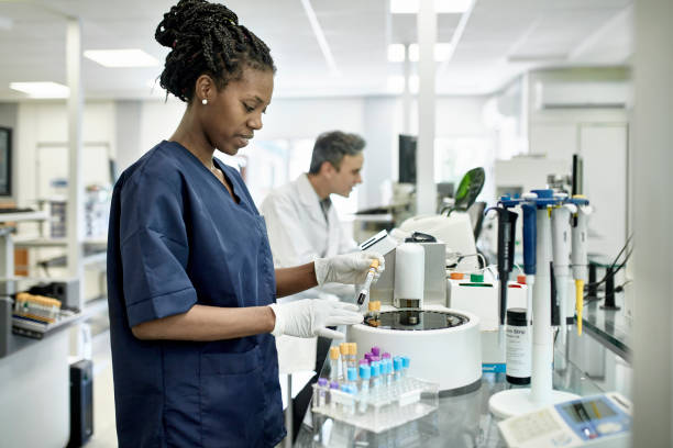 Young African Female Pathology Technician Working in Lab Smiling African female pathology technician in blue scrubs preparing test tubes for analysis in Buenos Aires clinical analysis laboratory. centrifuge stock pictures, royalty-free photos & images