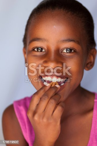 Little girl with big smile taking a bite of a nut.
