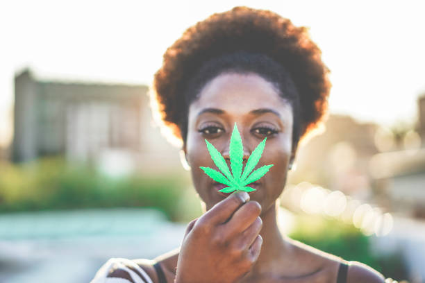 Young african girl holding marijuana leaf with - Cannabis medicine, healthy lifestyle and ecology concept - Focus on leaf stock photo