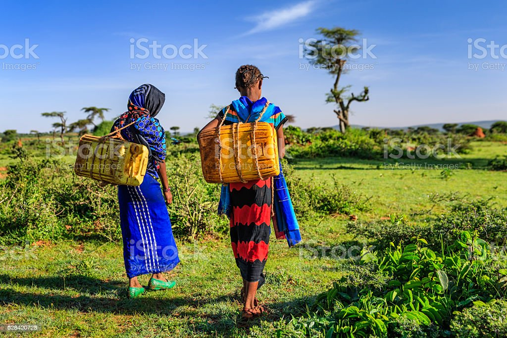 Young African girls carrying water from the well, Ethiopia, Africa stock photo