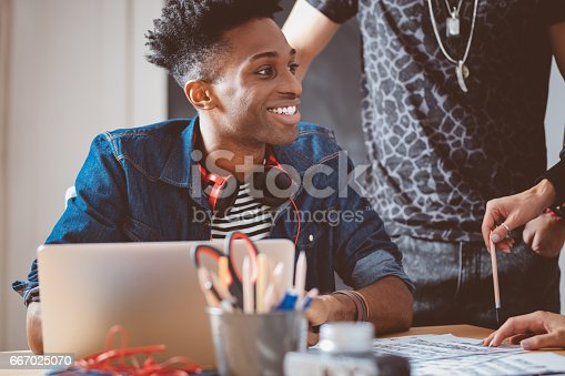 918746260istockphoto Young african guy in meeting with creative team 667025070