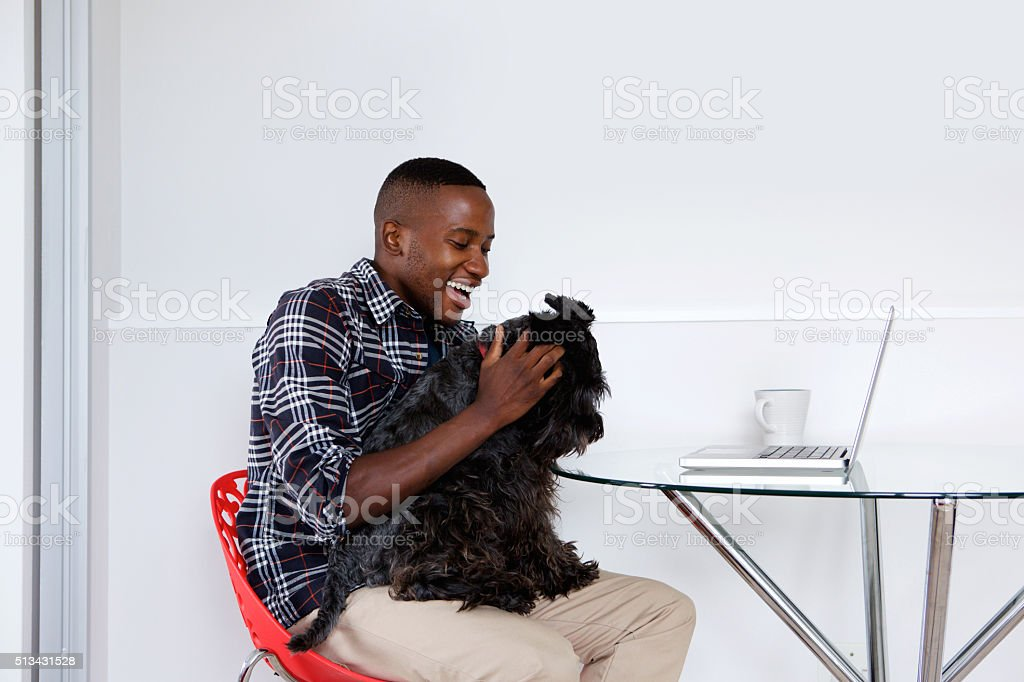 Young african guy playing with his pet dog stock photo