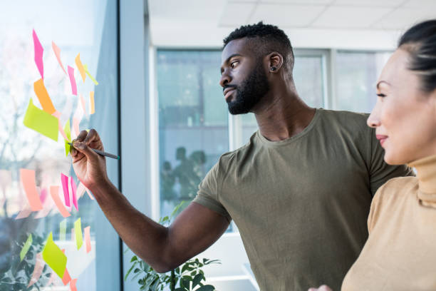 A young African man and an Asian woman brainstorming ideas in the office. There are sticky notes pasted on the large window and they are writing down the ideas. stock photo