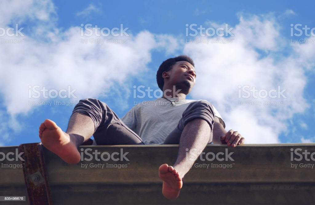 young african man barefoot summer vacation low angle view stock photo