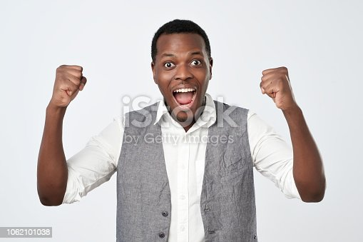 istock Young african man celebrating victory over gray background 1062101038