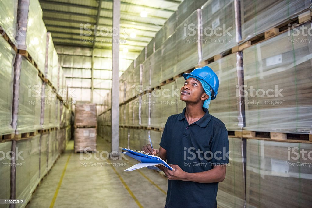 Young African man checking stock in aluminium plant stock photo