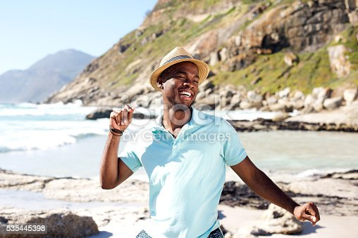 istock Young african man dancing at the beach 535445398