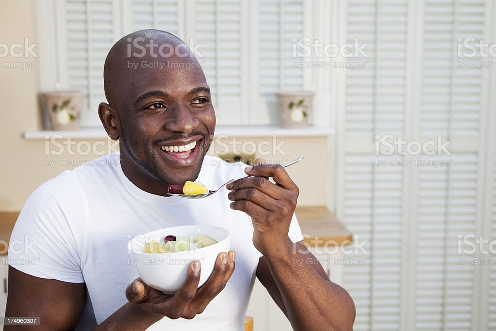 Young African man eating a healthy breakfast bowl of fruit royalty-free stock photo