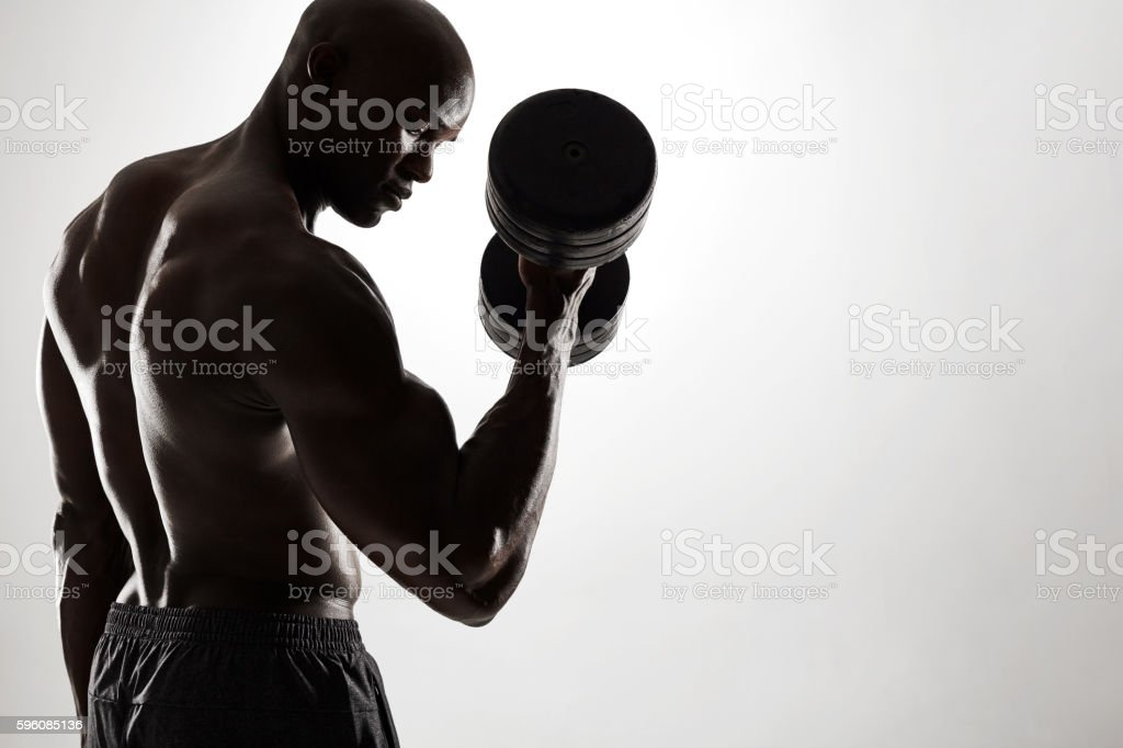 Young african man exercising with heavy dumbbells royalty-free stock photo