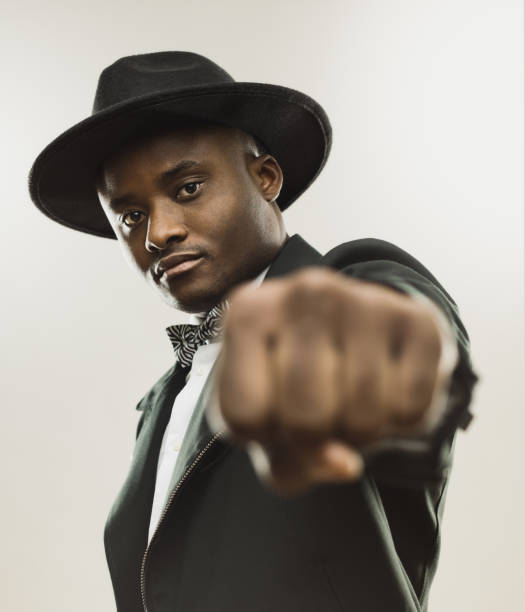 Young african man in suit showing his fist stock photo