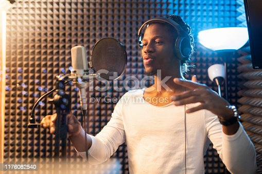 Young African man in white t-shirt and headphones standing by microphone and performing songs in studio of sound recording