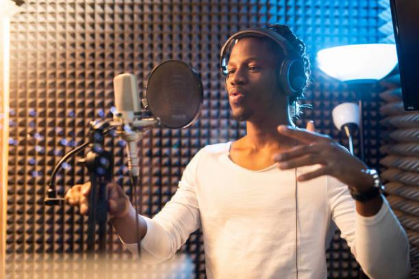 Junger afrikanischer Mann in weißem T-Shirt und Kopfhörern, die Songs im Studio vortragen – Foto