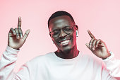 istock Young african man listening to music with earphones, dancing isolated on pink background 1093991968