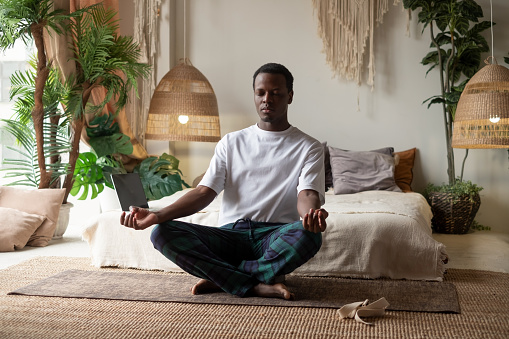 Young african man meditating sitting at his bedroom in the morning alone