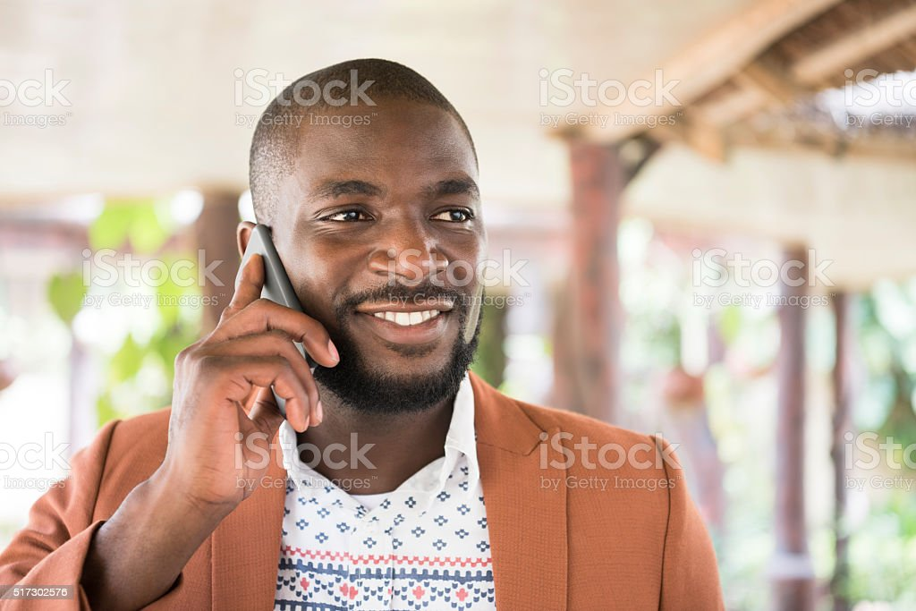 Young African man on cell phone, looking away smiling stock photo
