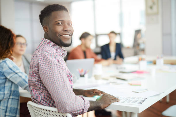 Young African Man Posing in Office Portrait of young African-American man smiling at camera while sitting at table in business meeting, copy space apprentice stock pictures, royalty-free photos & images