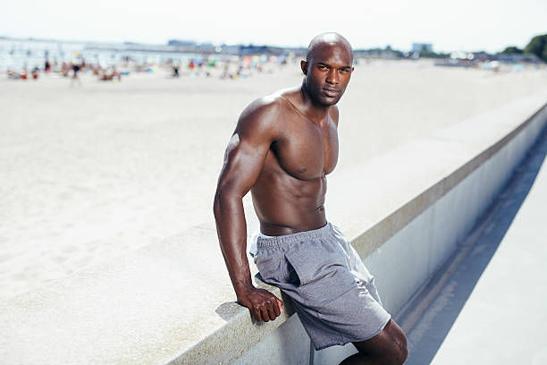 Young african man sitting on a beach embankment Portrait of muscular young african man sitting on a beach embankment looking at camera. Shirtless young man sitting on at promenade. shirtless male models stock pictures, royalty-free photos & images