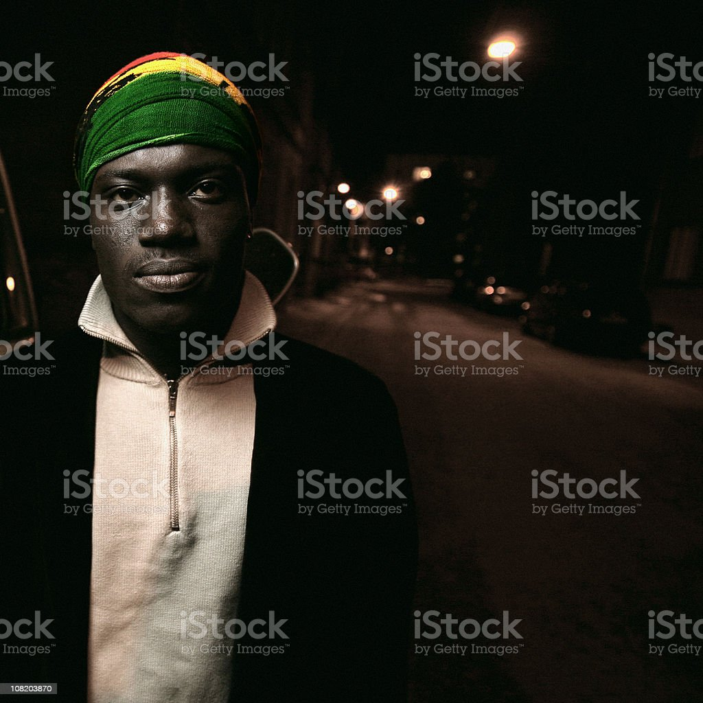 Young African Man Standing on Street at Night royalty-free stock photo