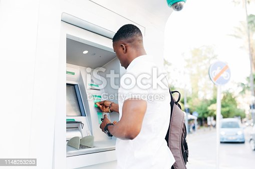 istock Young African man using ATM 1148253253