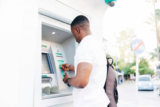 young african man using atm - банки и банкоматы стоковые фото и изображения