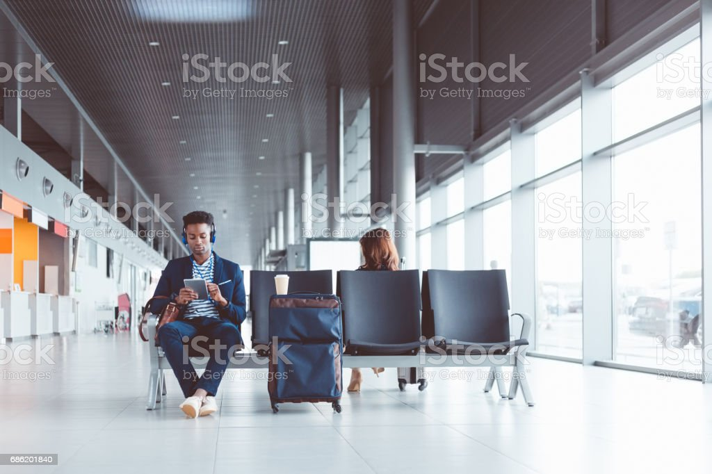 Young african man using digital tablet at airport lounge stock photo