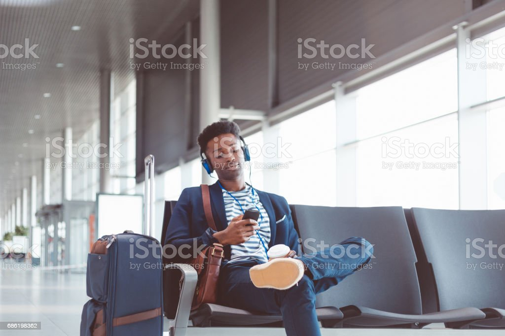 Young african man waiting for flight at airport lounge stock photo