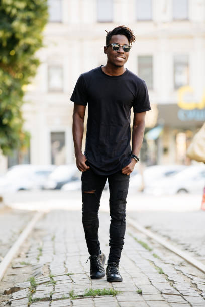 Young african man wearing black t-shirt in city street Young african man wearing black t-shirt in city street black shirt stock pictures, royalty-free photos & images