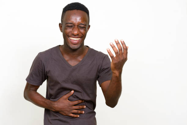 Young African man wearing brown shirt against white background stock photo