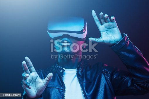 1090878574istockphoto Young african man wearing virtual reality goggles with hands up, isolated on black background 1150698628