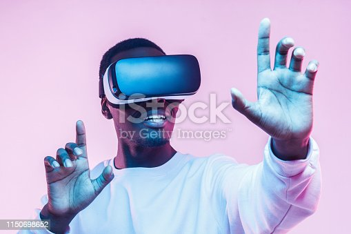1090878574istockphoto Young african man wearing  virtual reality goggles with hands up, isolated on pink background 1150698652