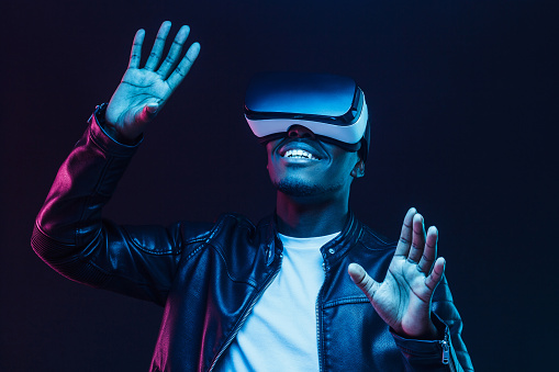 istock Young african man wearing virtual reality goggles with hands up, isolated on black background 1153003884