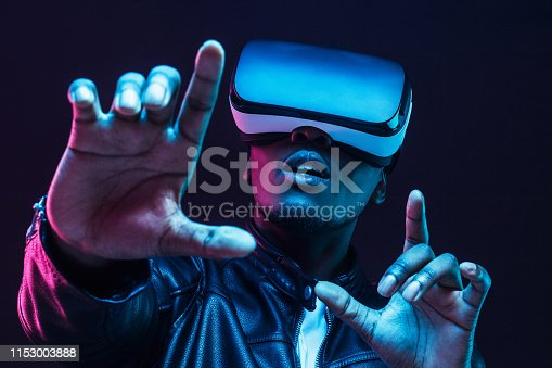 1090878574istockphoto Young african man wearing virtual reality goggles with hands up, isolated on black background 1153003888