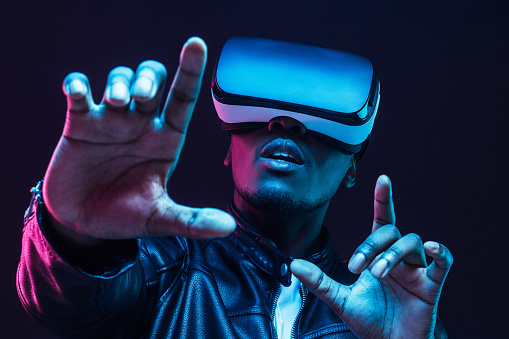 istock Young african man wearing virtual reality goggles with hands up, isolated on black background 1153003888