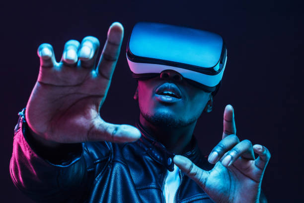 Young african man wearing virtual reality goggles with hands up, isolated on black background Young african man wearing virtual reality goggles with hands up, isolated on black background arts culture and entertainment stock pictures, royalty-free photos & images