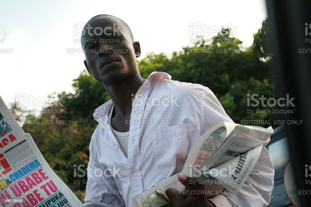 Young african men, offers newspapers to drivers in traffic jam. stock photo