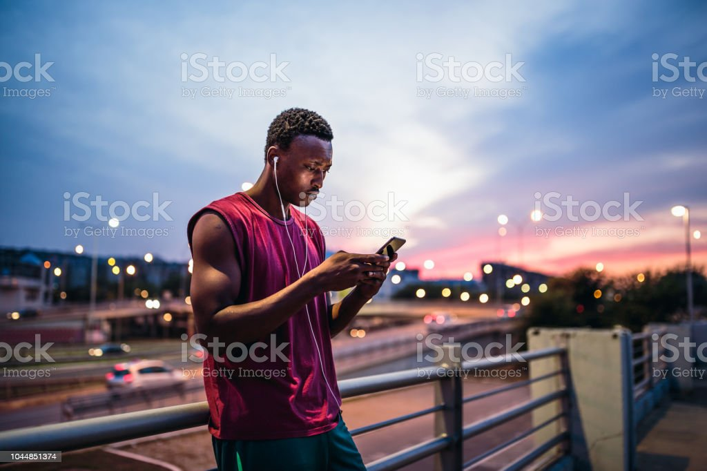 Young African men resting after training outdoors, using mobile phone stock photo