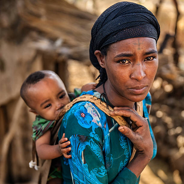 young african mother carrying her baby on back, east africa - horn of africa stock photos and pictures