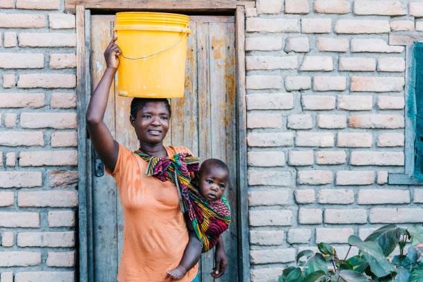Junge afrikanische Mutter mit Baby, das Wassereimer auf dem Kopf trägt – Foto