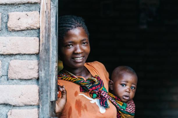 Junge afrikanische Mutter mit Baby in der Tür – Foto