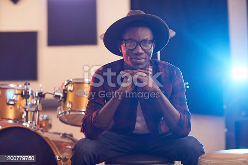 Portrait of contemporary African man looking at camera and smiling cheerfully while posing in music recording studio