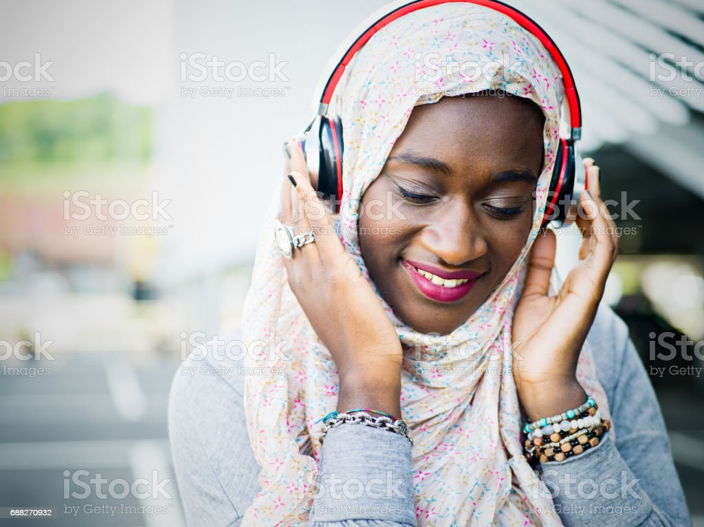 Young African Muslim woman listening to music by headphones stock photo