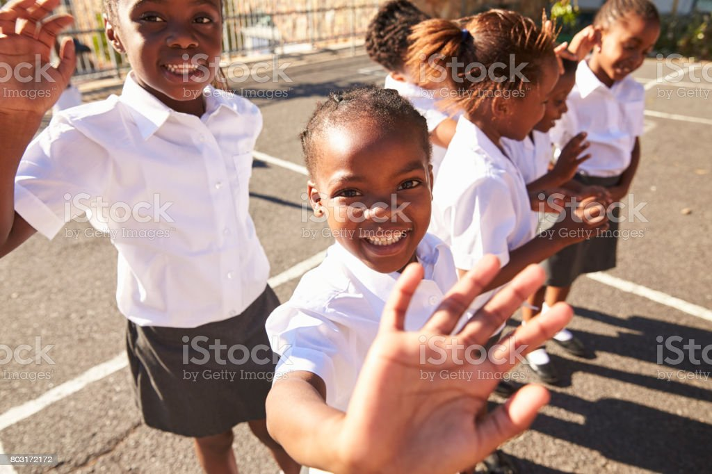 Young African schoolgirls in a playground waving to camera stock photo