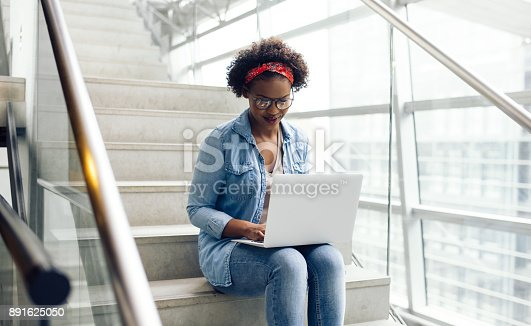 istock Young African student sitting on campus stairs using a laptop 891625050